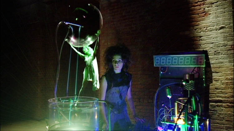 In the foreground, a hologram of a woman holding a transluscent bubble. In the background, a woman surrounded by cables.