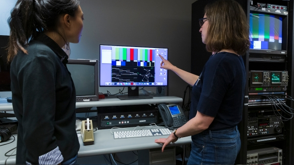 Two MIAP students looking at color bars on computer monitor in lab