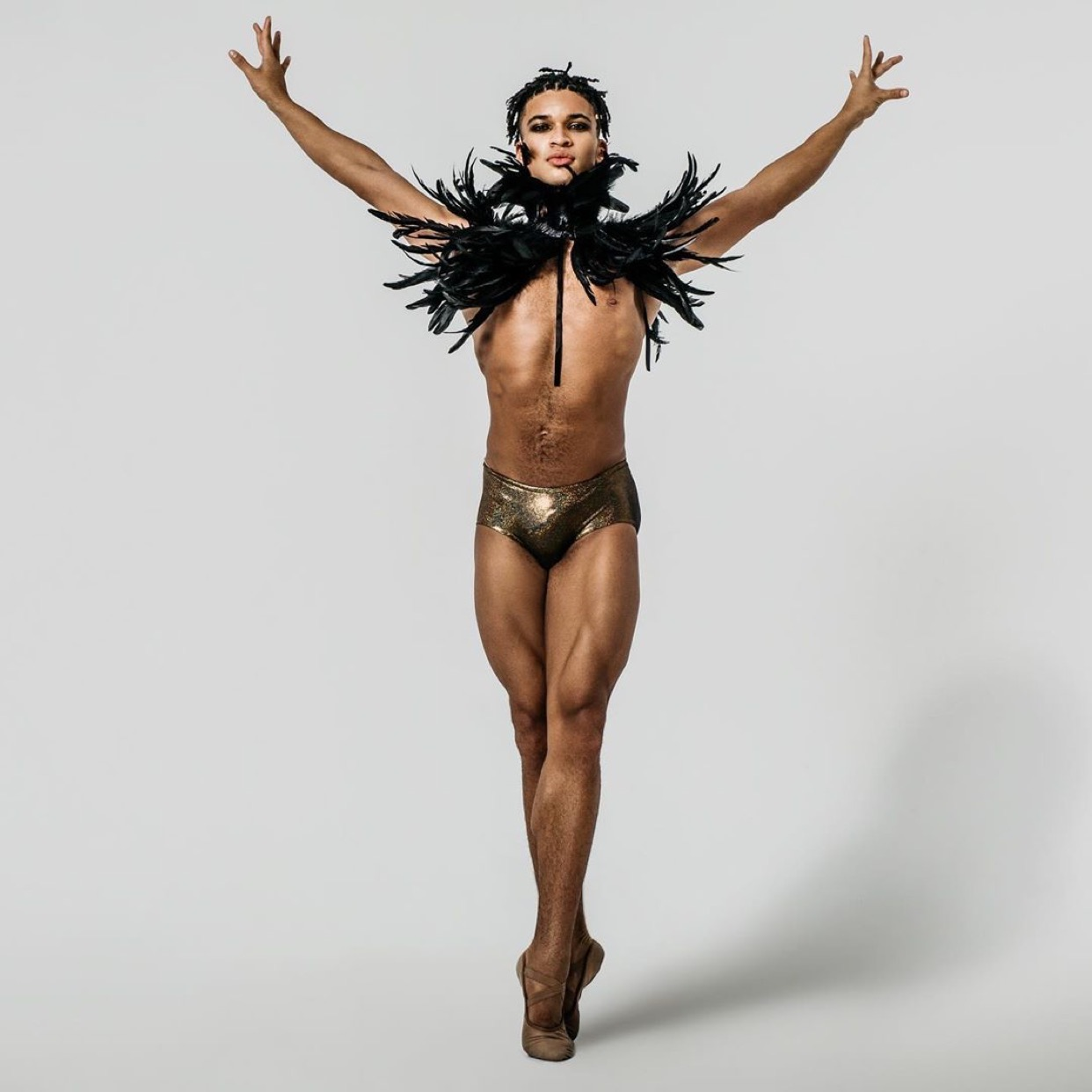 Dancer in white background wearing black feathers on shoulders and wearing ballet shoes.