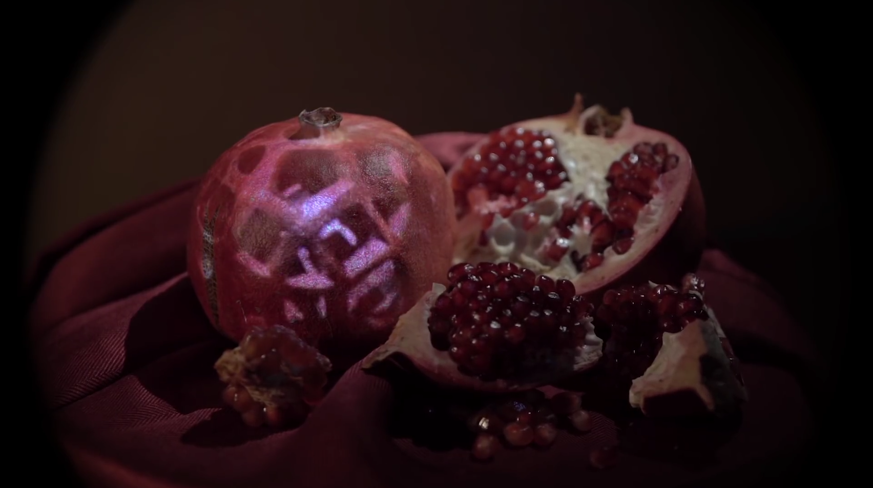 "Filmstill from, ""I Wish the Wars Were All Over."" Image of cut opened pomegranate with seeds in a dimley light room with a flickering light."