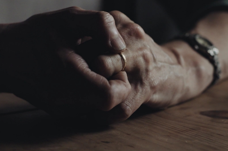 Film Still: close up of woman's hands clapsed together, resting on a table
