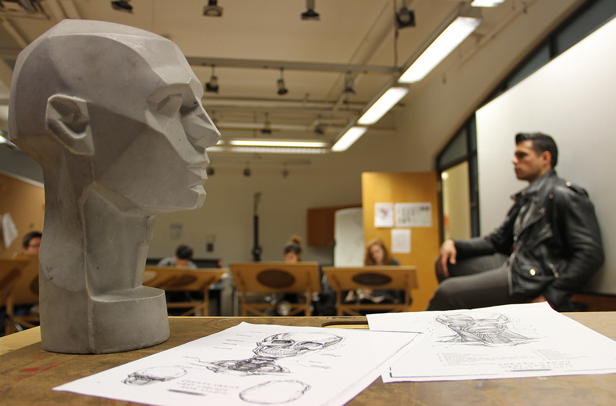 Bust of head on the left of frame on a desk with life drawing model on the right in the background.