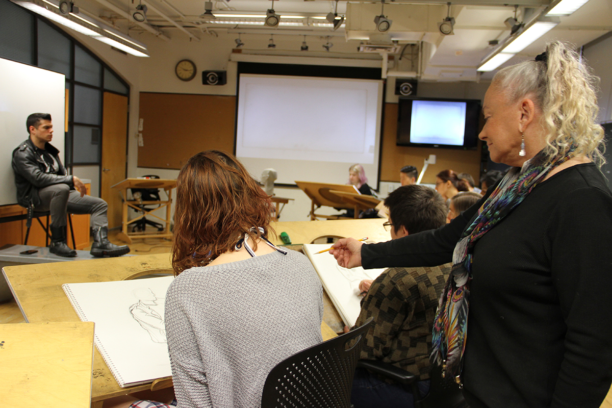 Professor Sherry Camhy teaching a group of students how to draw a live model.
