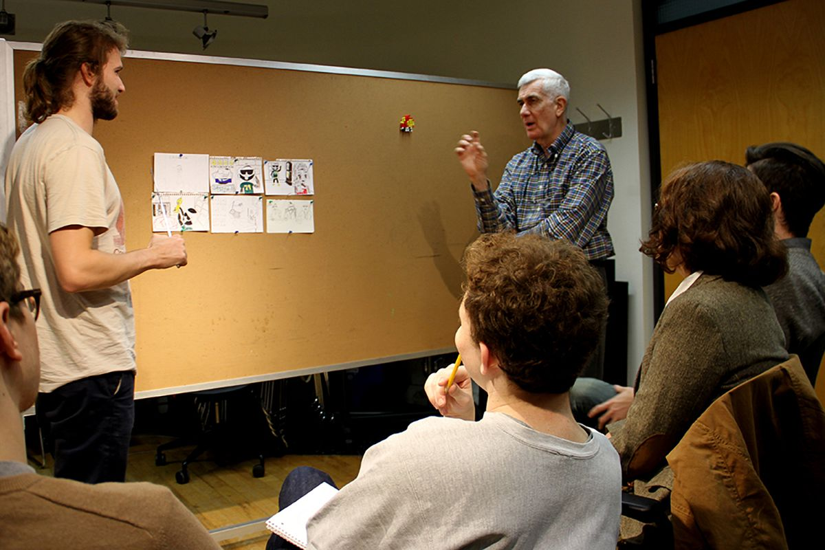 Professor John Canemaker looking over storyboard drawings pinned to corkboard with students looking on.