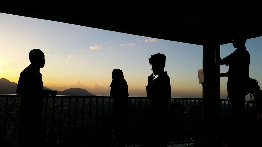 "Film still from ""Cross My Heart."" Image of 4 people standing on a balcony with beautiful mountains and sky."