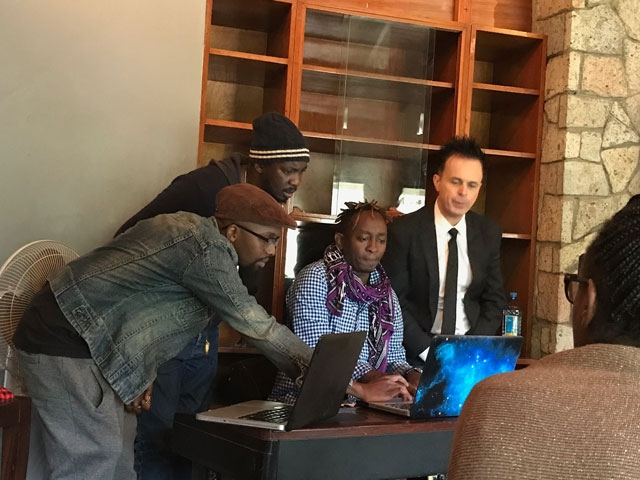 Eric Wainaina and other creative artists discussing a piece