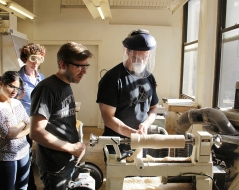 students learning to operate a lathe in the woodshop.