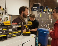 a student checking out hardware tools in the shop.