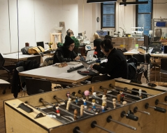 people working in the lounge with the foosball table in the foreground