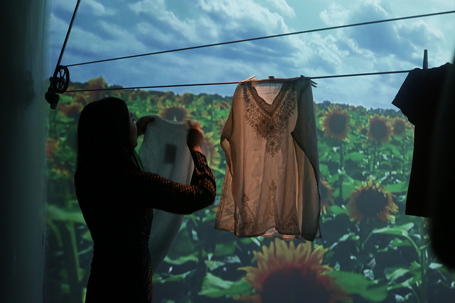 Camper hangs clothes on clothesline in front of projection of Sunflower patch