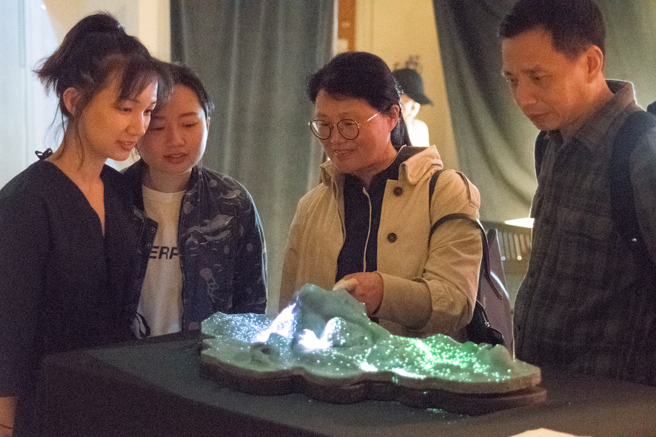 ITP student and guests look at light-up landscape model