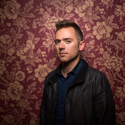 A serious faced man in black against a flowery wallpaper