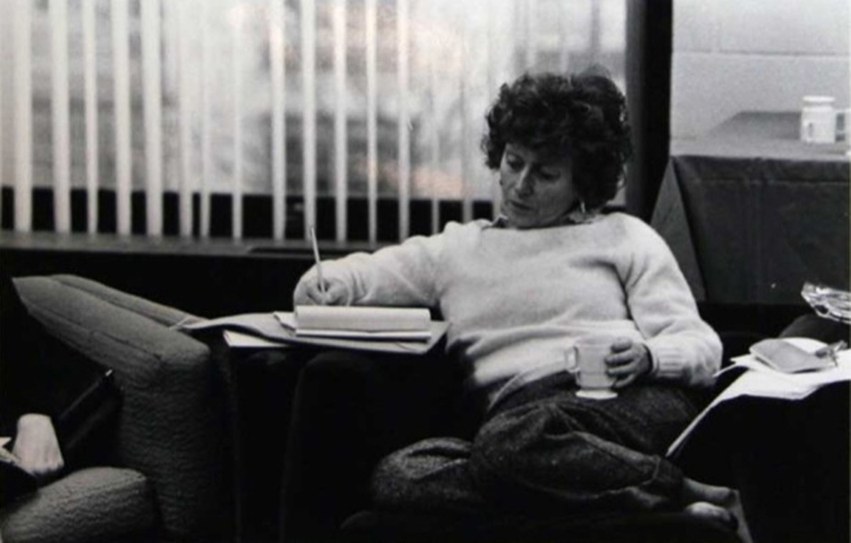 a younger Red Burns sitting on a couch with a mug writing on a notepad
