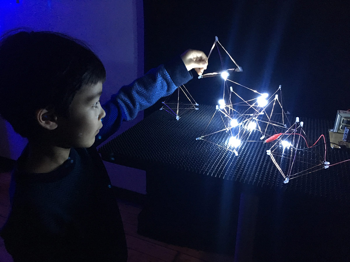 a boy playing with metal triangle shapes lit up by LED's