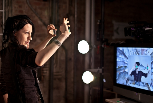A woman holding up 2 objects as a sensor detects the location of the objects on a screen.