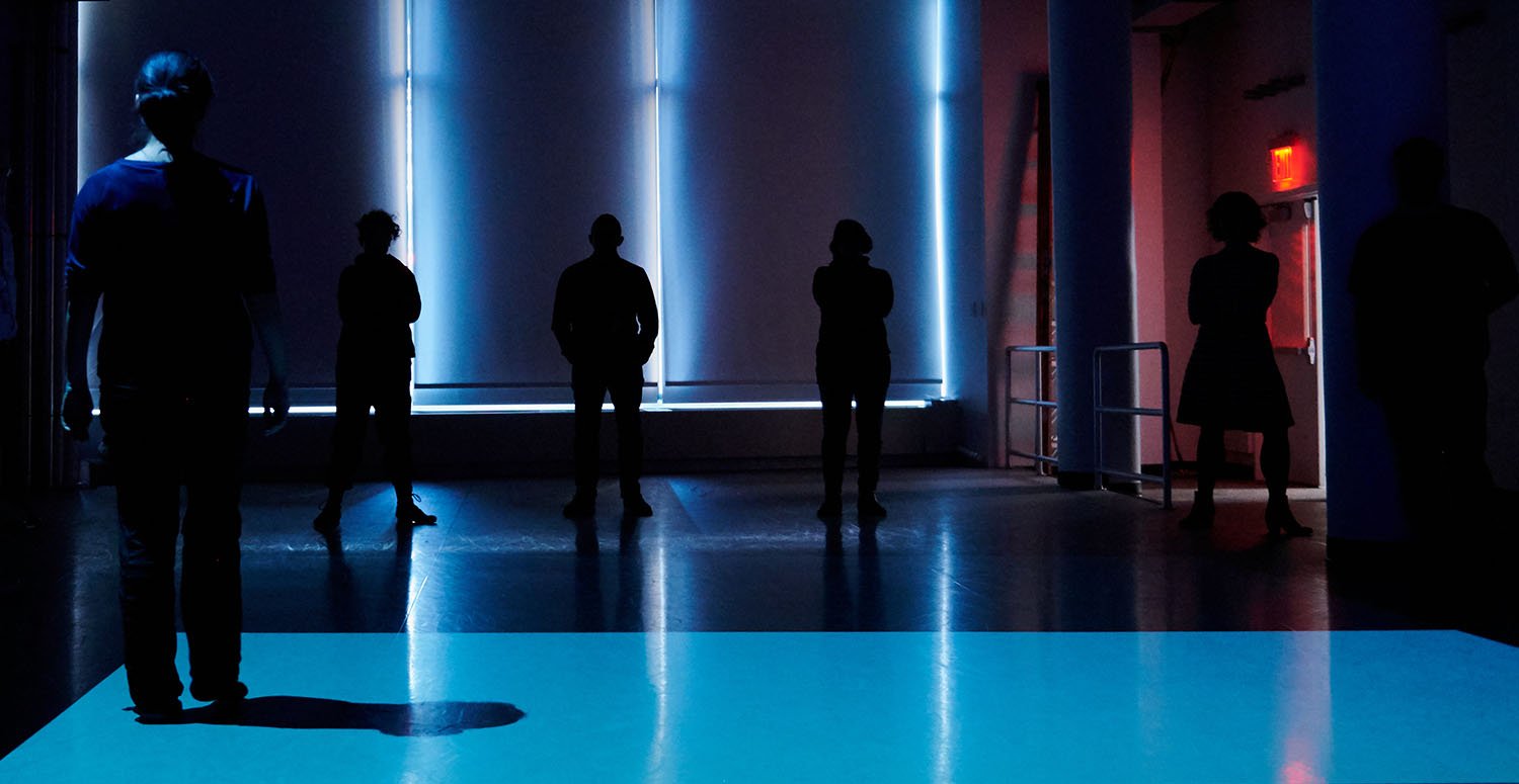 Dancers stand in an artfully lit room