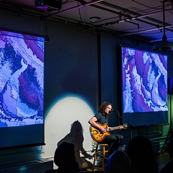 Student plays guitar in front of dynamic visuals