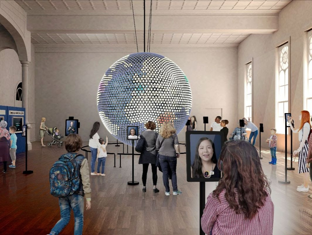 people walk around a museum with a globe in the center