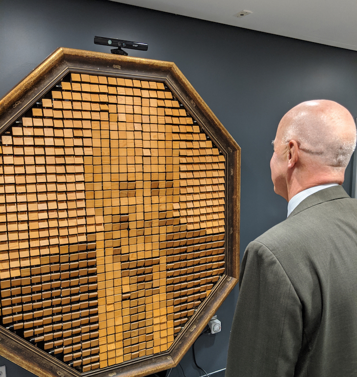 Andy Hamilton stands in front of the wooden mirror