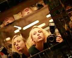 a woman holding a camera reflected in many mirrors