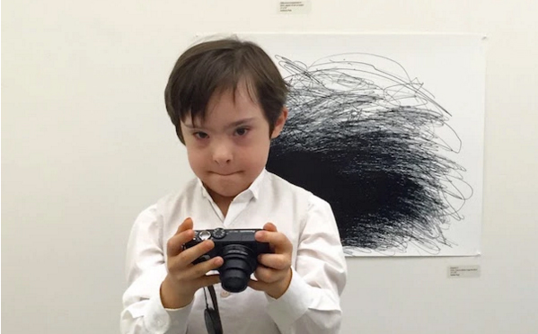 a boy holding a camera with a black scribble drawing in the background