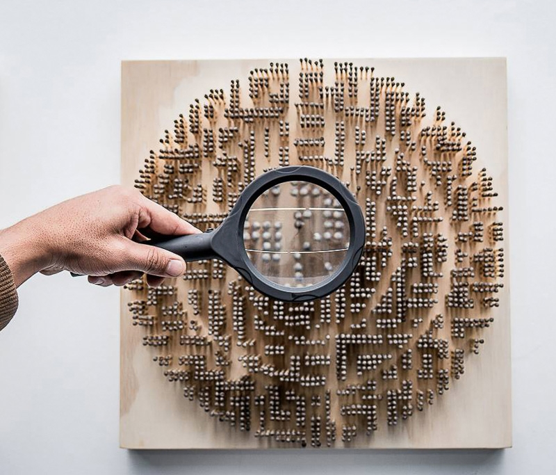 A circle arrangement of standing matchsticks, with someone holding a magnifying glass in the center