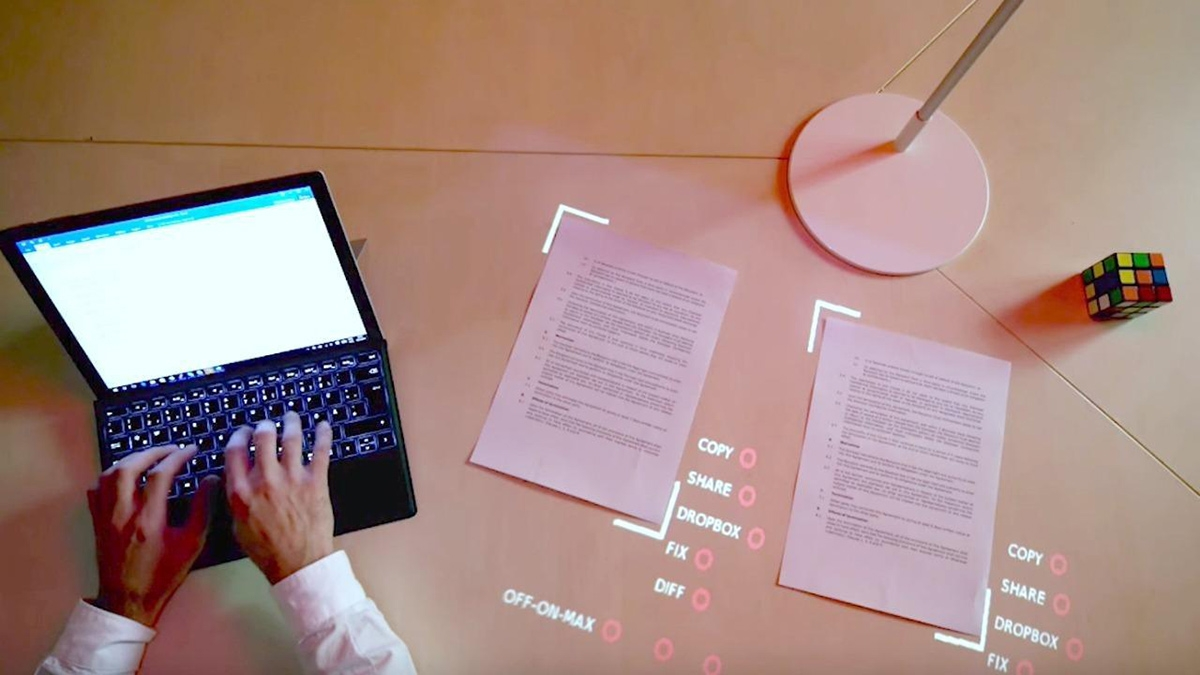 Aerial view of a person typing on a laptop with papers, a lamp and rubic's cube with digital words projected around the papers