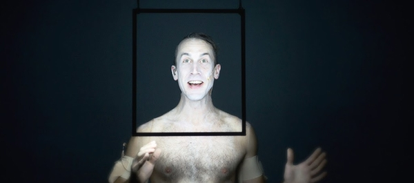 a smiling, shirtless man with his face painted white standing behind a black frame
