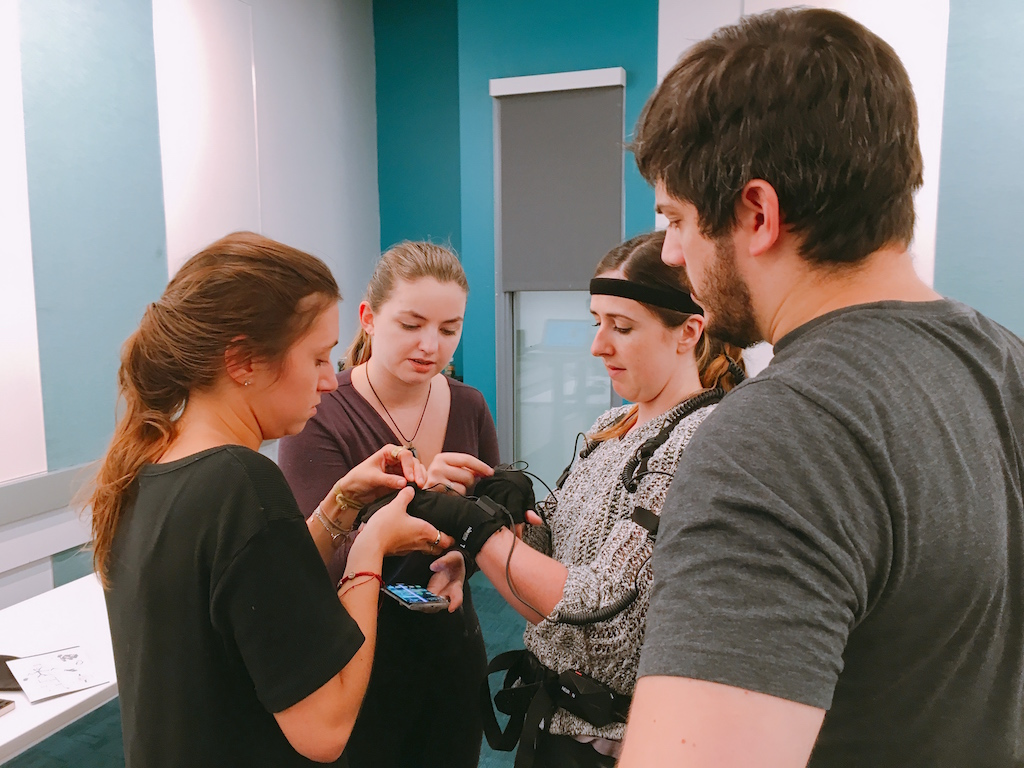 Photo of four students working together with virtual reality gear; photo by Christina Hall