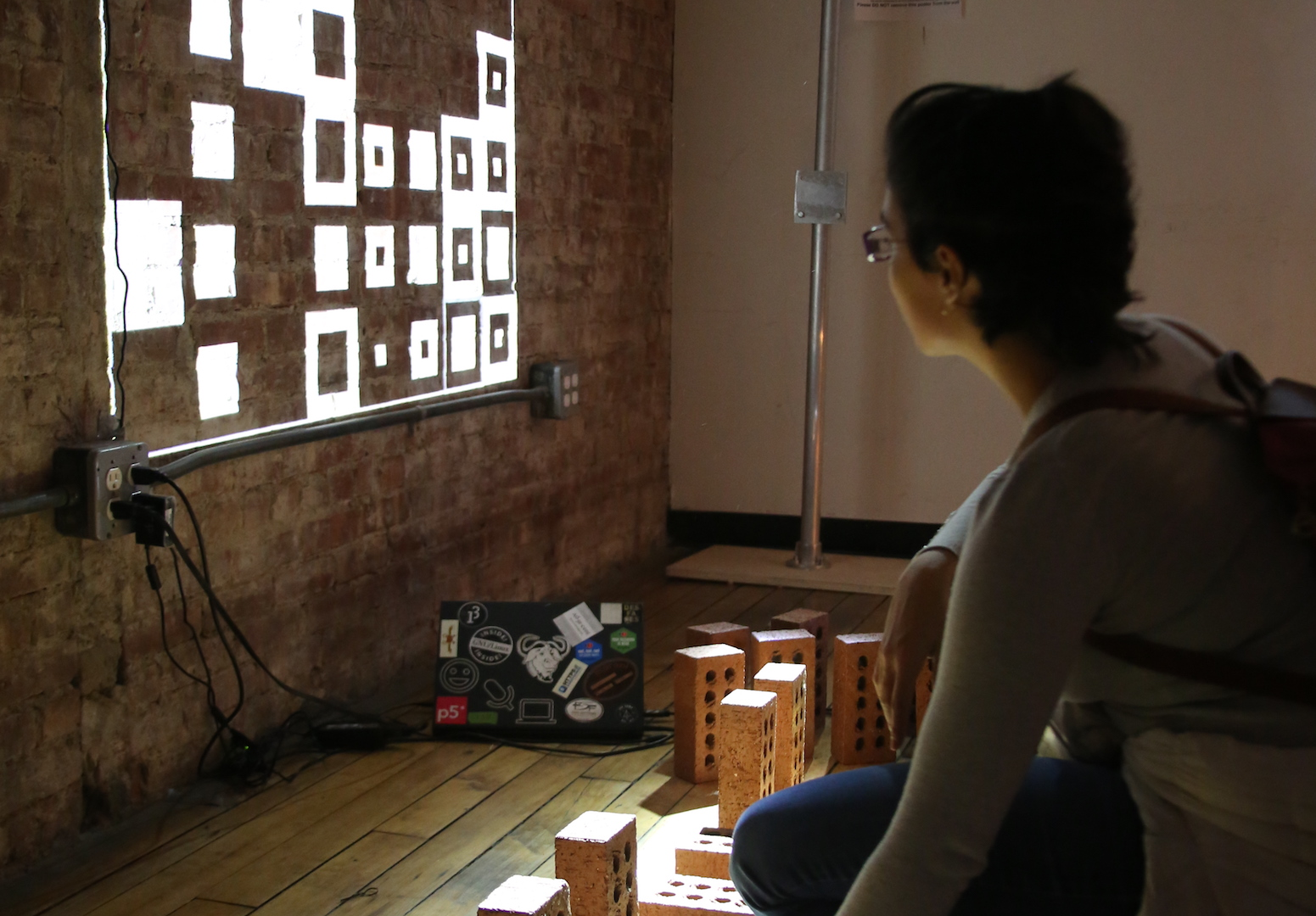 a person interacting with bricks while looking at black and white squares projected on the wall