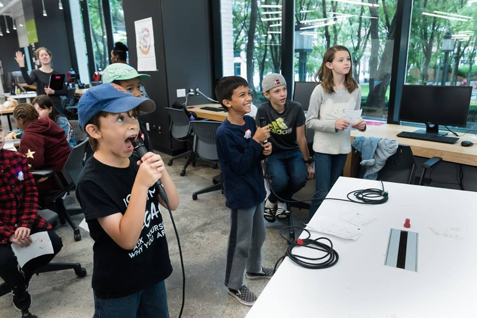 Four kids having fun while interacting with an installation holding microphones
