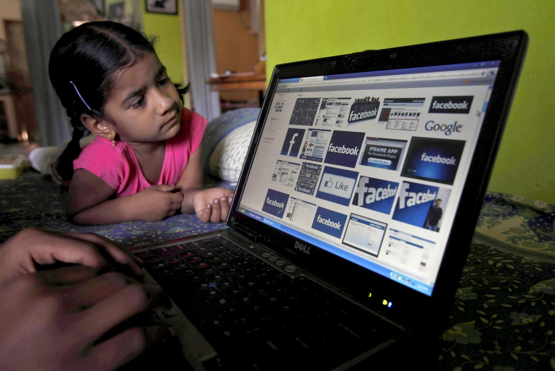 A child looks at a laptop displaying Facebook logos in Hyderabad, India.