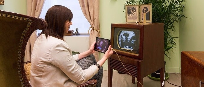 A woman holding an Ipad in front of an antique TV set made of wood