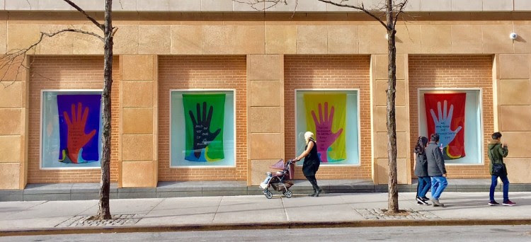 Window displays at NYU Kimmel building of banners showing hands