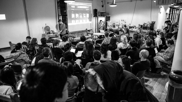 Black and white image of ITP students in the lounge listening to a lecture