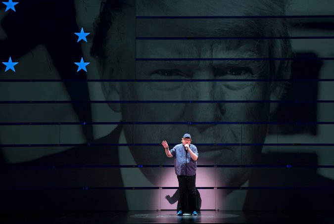 Michael Moore speaking on a big stage against the backdrop of Donald Trump's close up image