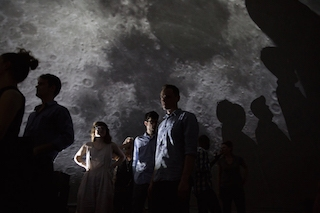 3 people with their shadows projected against a closeup of the moon in the background