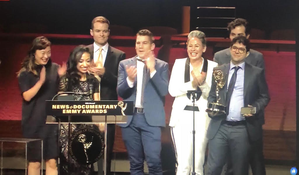 A team of people including Yasmin and Elie standing onstage accepting their award at the News and Documentary Emmys