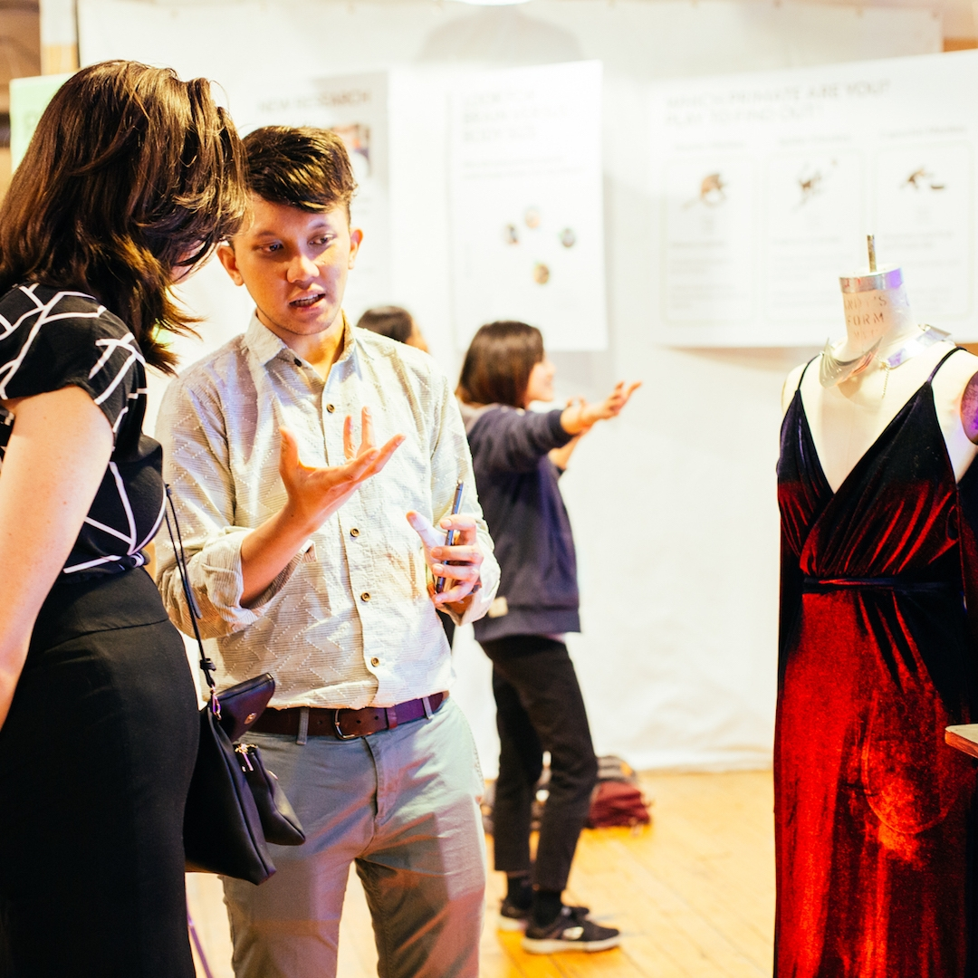 Student explains project of dress on mannequin to guest