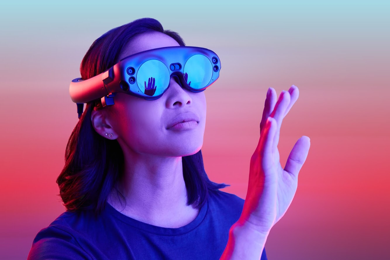 Woman looks through VR lenses, lifting hand as if to see something only she can see