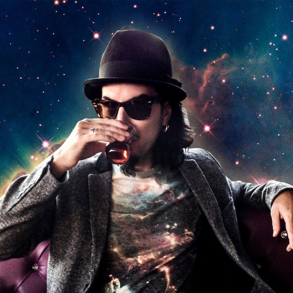 Image of Memo Akten, sipping a drink on a leather couch in outer space