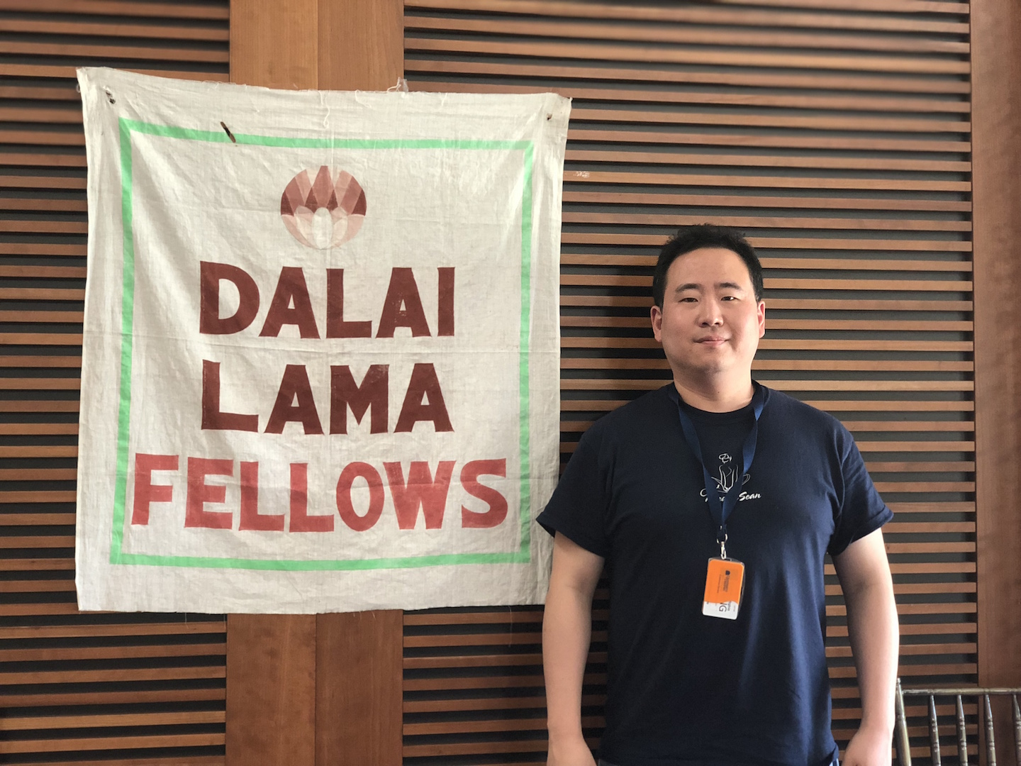 Image of Sean Kim in front of a poster that reads Dalai Lama Fellows at the Conference