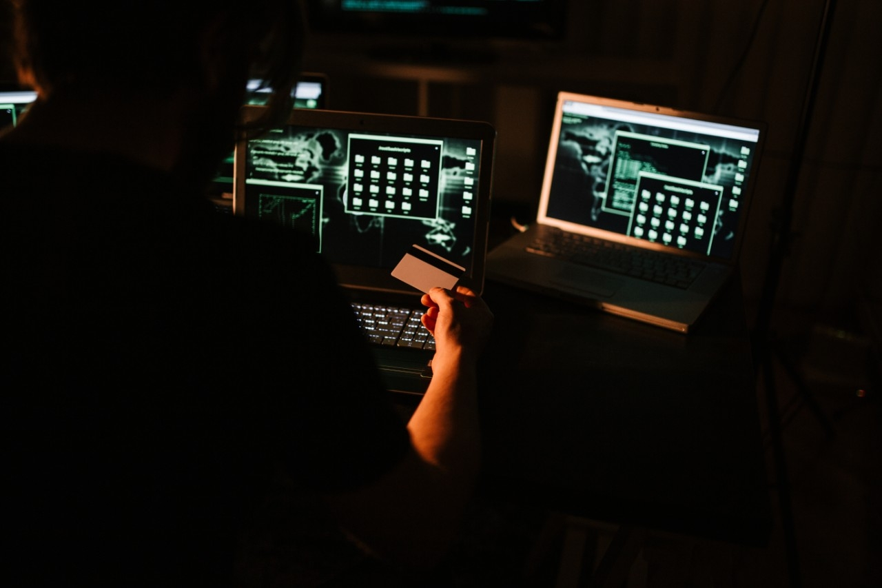 a person sitting in a dark room in front of 2 computer screens