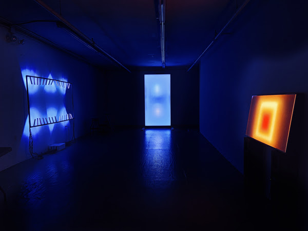 3 light installations in a dark gallery space