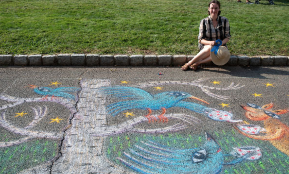 a woman sitting on the curb next to an intricate chalk drawing of a tree and bird