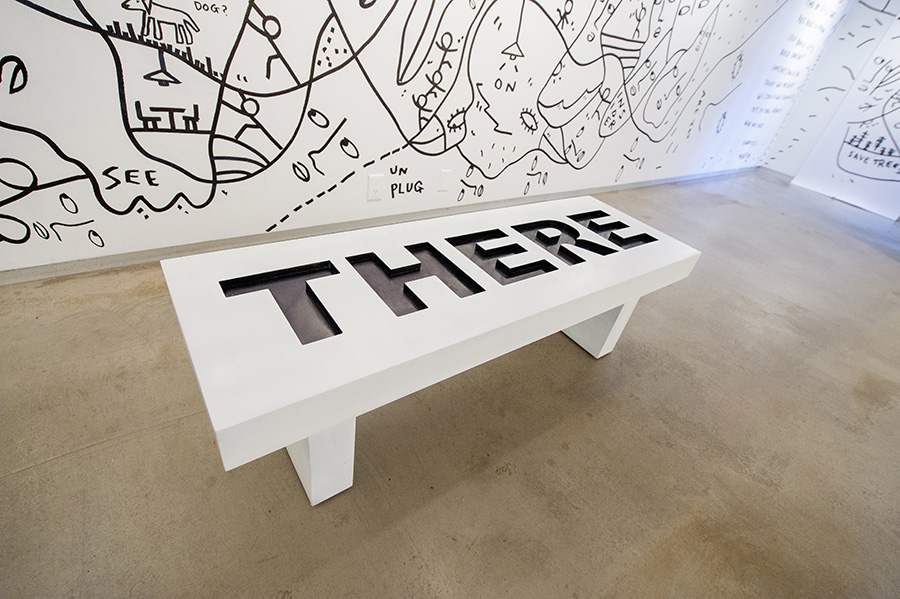 a bench that shows the word There with black drawings on the wall