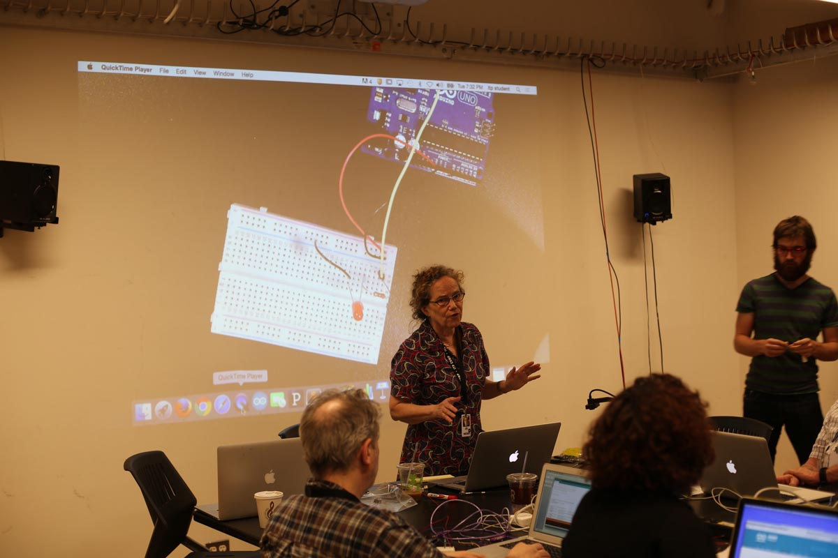 a woman giving a lecture about the Arduino and breadboard