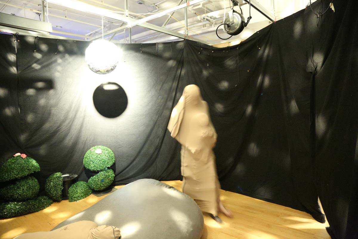 2 people with nylon covering their bodies in a black curtained room with lights from a disco ball, beanbag chair and plants