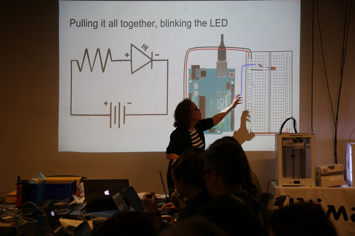 a woman giving a lecture and pointing to a projection of an Arduino and LED