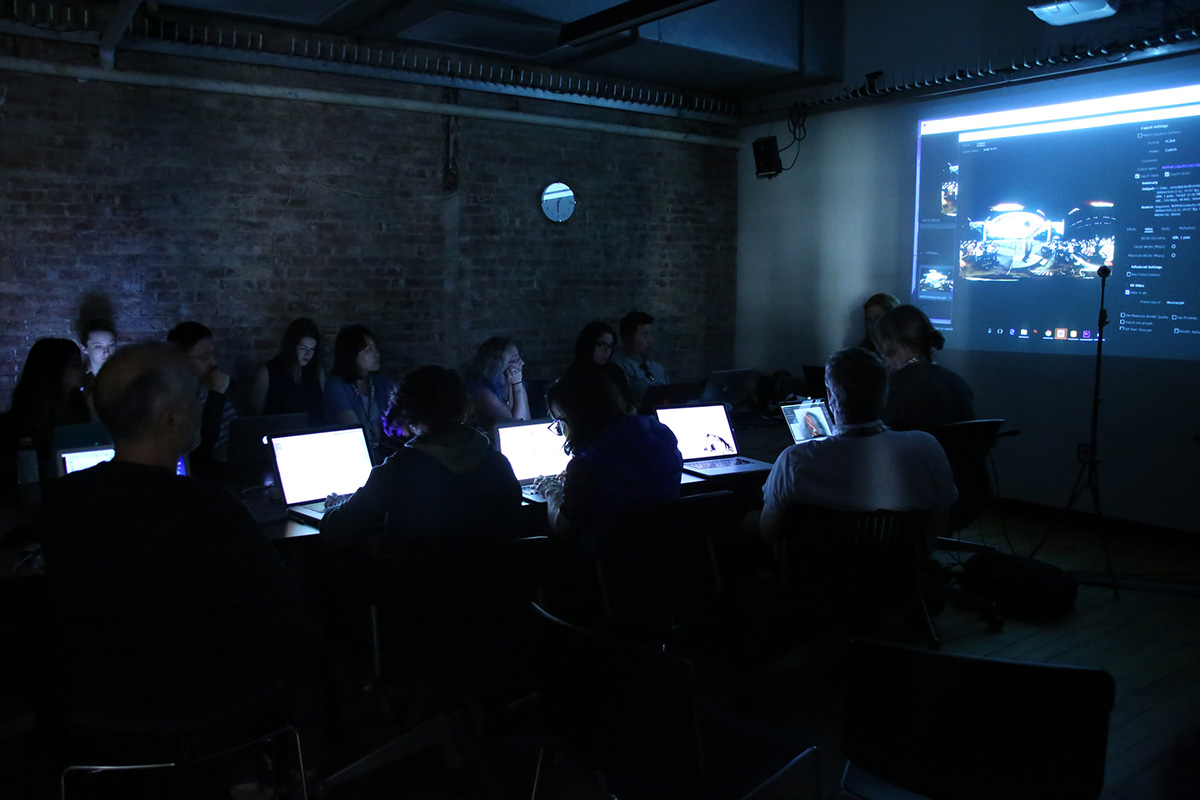 a lecture in a dark room with laptops illuminated